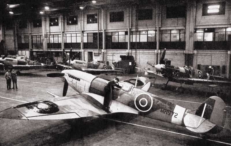 mechanic finishing off a spitfire in the assembly shop of an aircraft factory